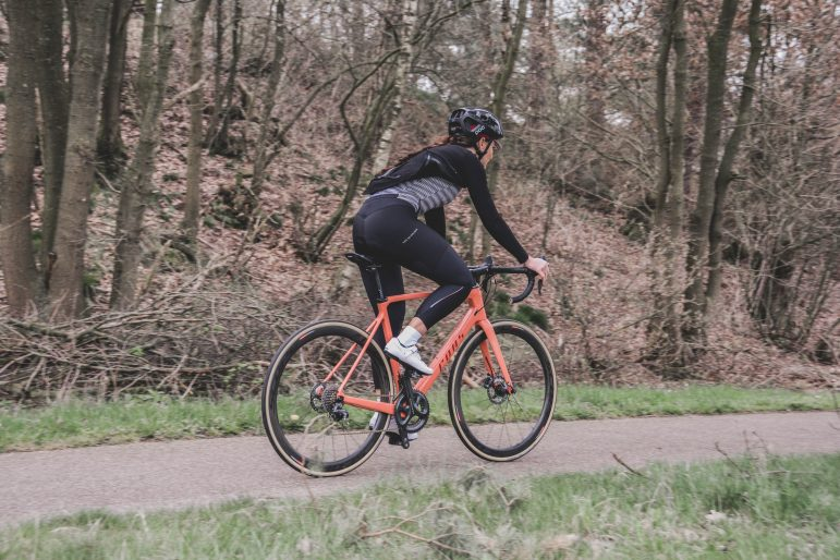 Young person on mountain bike along wooded path